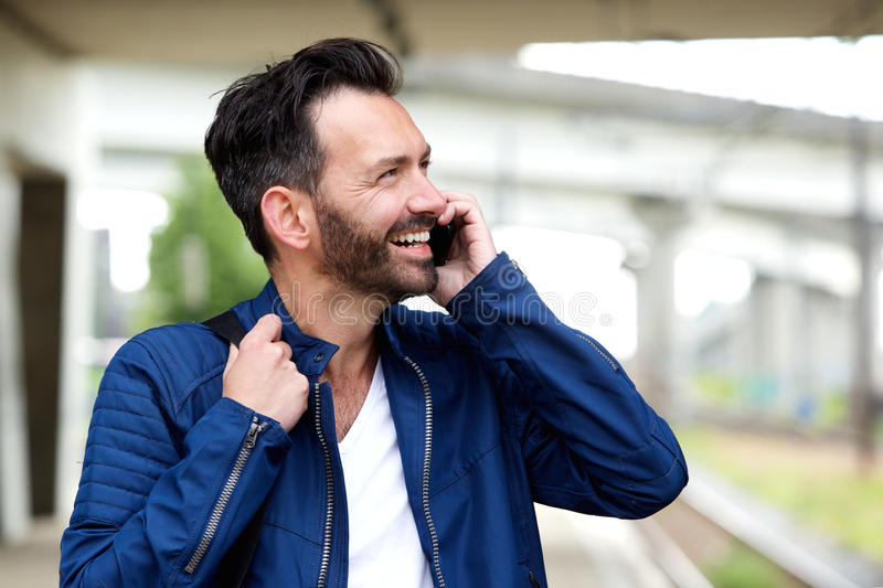 Cheerful mature man talking on mobile phone. Close up portrait of cheerful mature man standing outdoors and talking on mobile phone stock photos