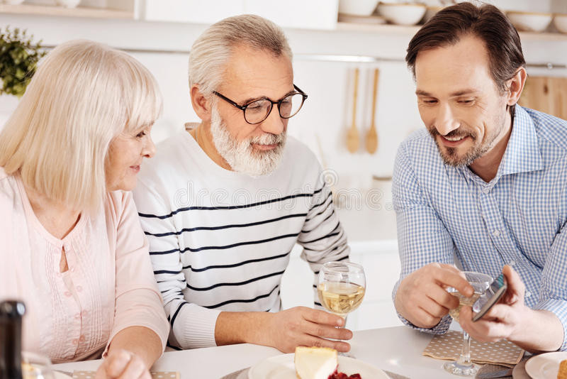 Cheerful mature son enjoying family dinner at home royalty free stock photography