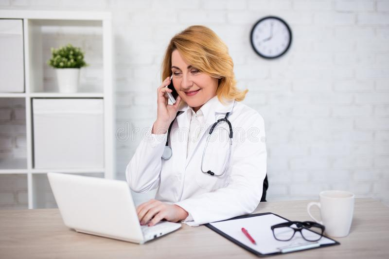 Cheerful mature woman doctor or nurse working with laptop and talking by phone in office. Cheerful mature woman doctor or nurse working with laptop and talking stock images