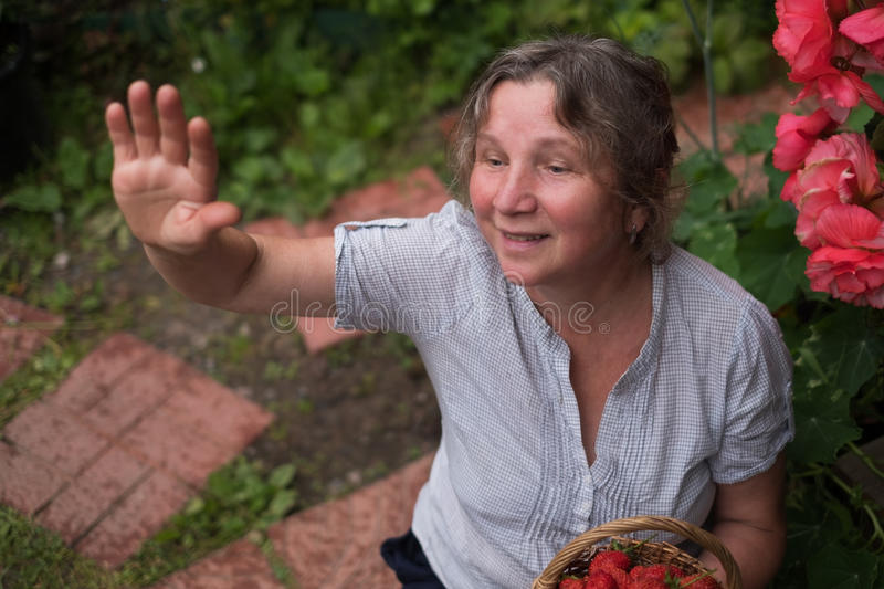 Cheerful mature woman sits in the garden and waving to friends royalty free stock image