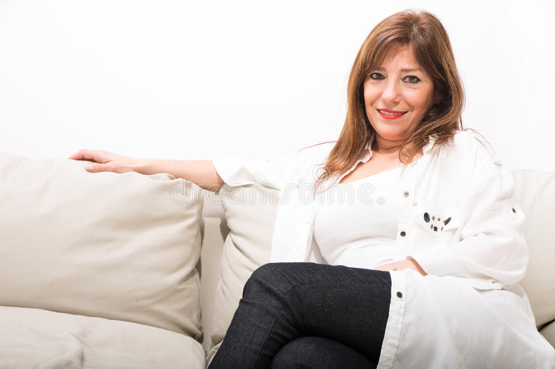 Cheerful mature woman on the sofa at home stock images