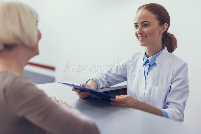 Cheerful medic is greeting patient in clinic hall royalty free stock photos