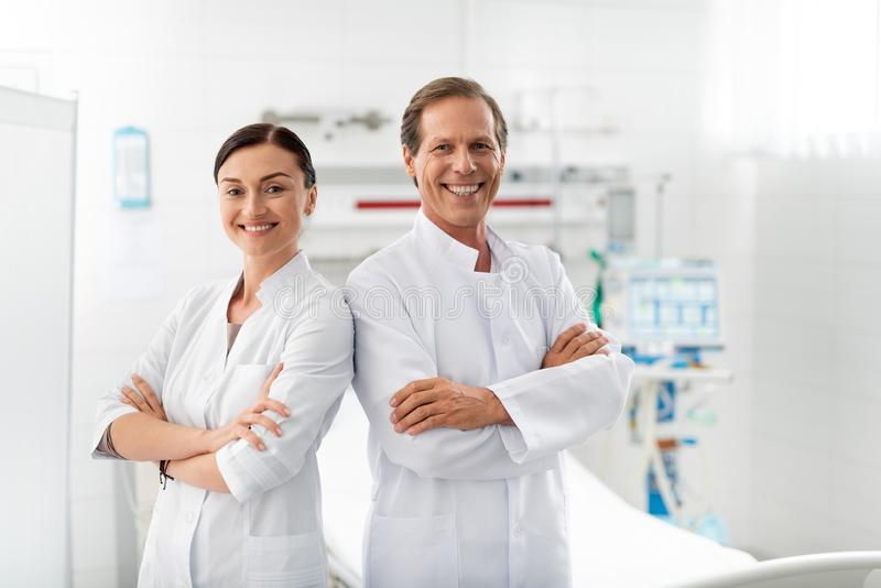 Cheerful medical workers with crossed hands posing in hospital room stock image