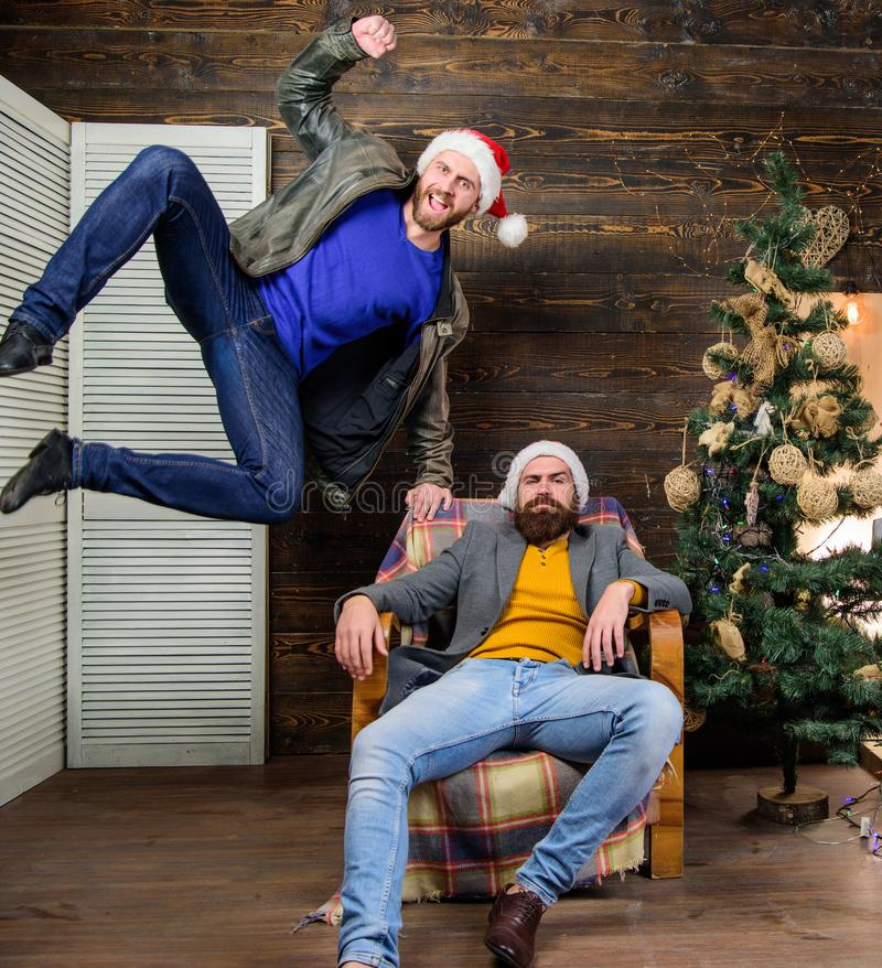 Cheerful men having fun near christmas tree. Christmas fun. Friends having fun on christmas eve. Can not hold back. Emotions. Emotional coup. Cant wait. Change royalty free stock photography