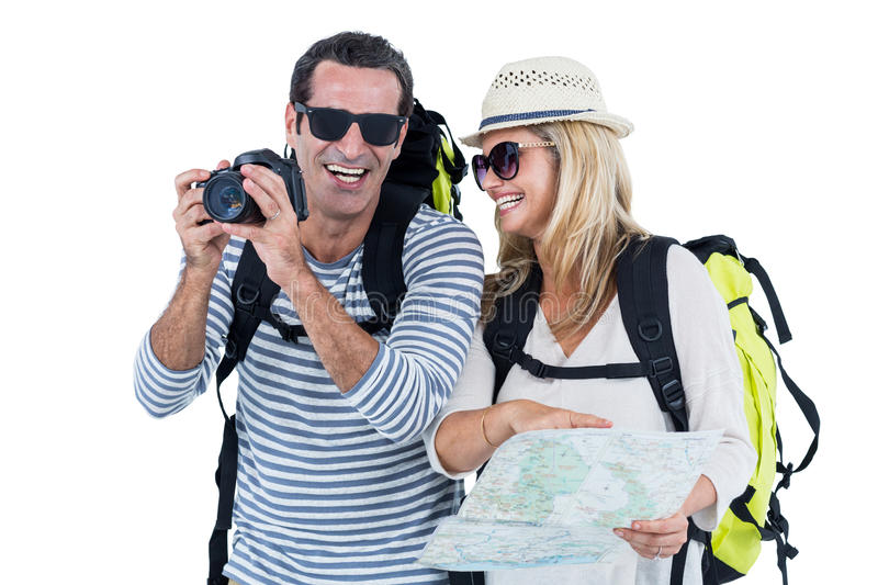 Cheerful mid adult couple carrying luggage. Against white background royalty free stock photo