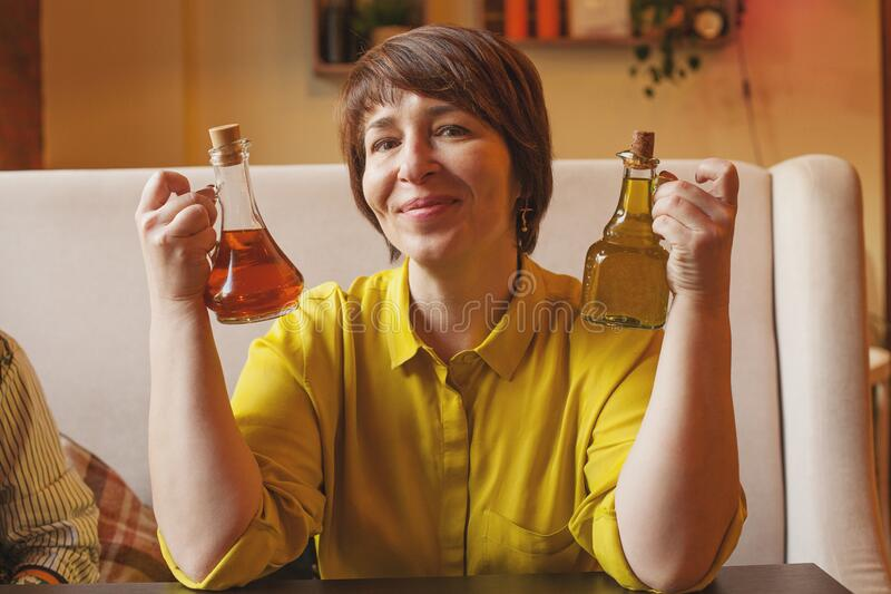 Cheerful mid adult woman with olive oil and balsamic vinegar bottles in italian cafe.  stock image