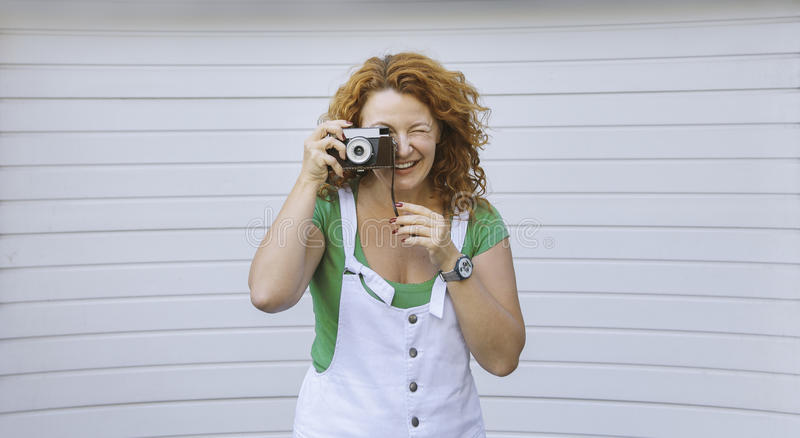 Cheerful middle aged lady using vintage camera. Day, outdoor . Happy red hair woman taking picture on retro camera royalty free stock photo