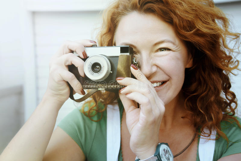 Cheerful middle aged lady using vintage camera. Day, outdoor . Happy red hair woman taking picture on retro camera stock photography