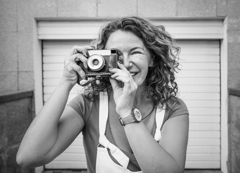 Cheerful middle aged lady using vintage camera. Day, outdoor stock photo