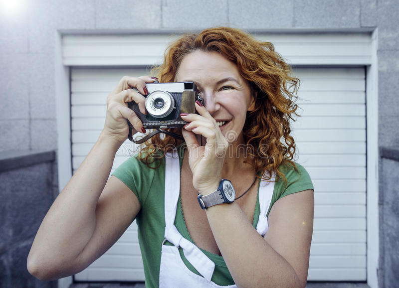 Cheerful middle aged lady using vintage camera. Day, outdoor royalty free stock images