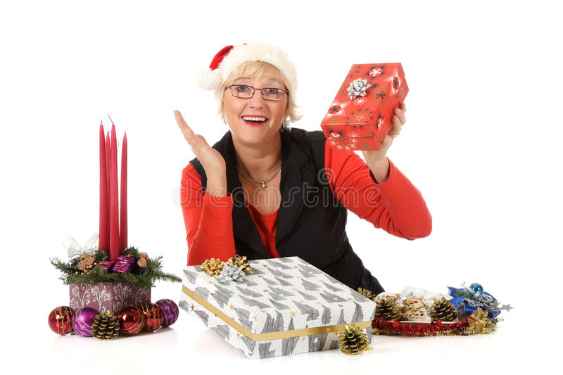 Cheerful middle aged woman, Christmas gifts. Cheerful caucasian middle aged woman holding and wondering about Christmas gifts. Traditional cake, decoration and royalty free stock images