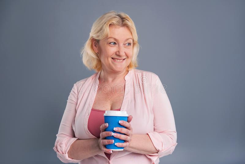 Cheerful middle-aged woman holding blue coffee cup. Caffeine addicted. Upbeat middle-aged woman holding a blue coffee cup and smiling happily while standing stock photography