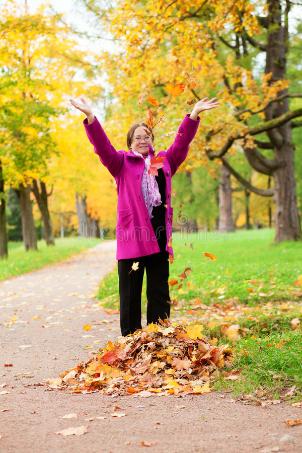 Cheerful middle aged woman playing with leaves. Cheerful middle aged woman playing with autumn leaves by fall stock photography