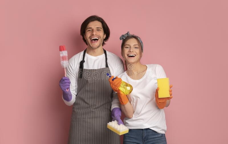 Cheerful Millennial Couple With Cleaning Supplies In Hands Over Pink Background. Ready To Clean. Portrait Of Cheerful Millennial Couple Holding Cleaning Supplies royalty free stock photography