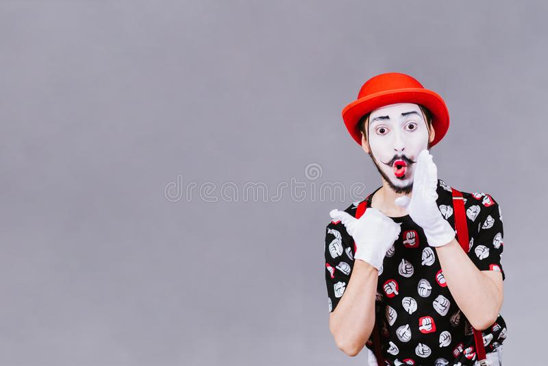 Funny mime posing near a gray background. Cheerful mime posing near a gray background stock image