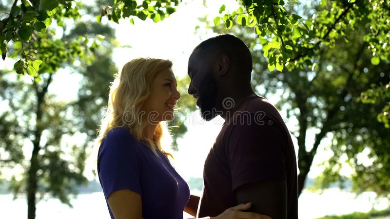 Cheerful mixed race couple looking at each other with love, happy to be together royalty free stock image