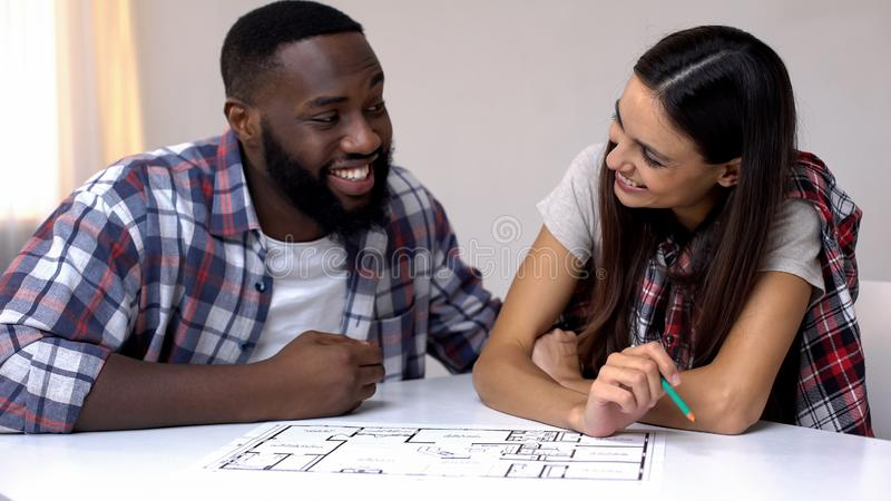 Cheerful mixed-race family planning interior design of new house, relationship stock image