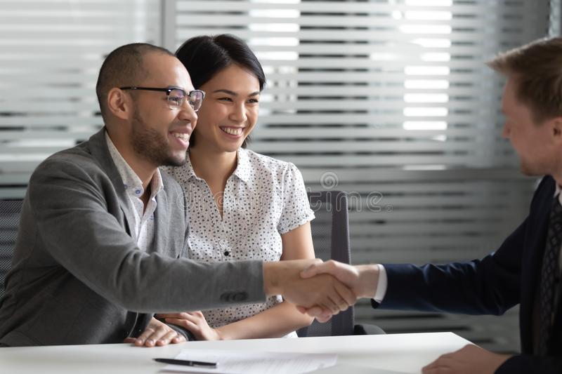 Cheerful mixed race married spouse shaking hands with real estate agent. stock photo