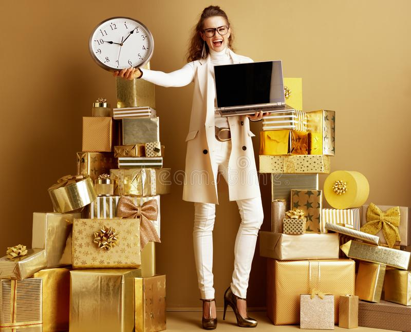 Cheerful modern woman showing laptop blank screen and clock stock photography