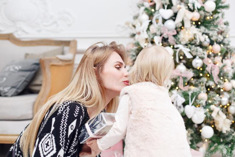 Cheerful mom embraces her cute baby daughter . Parent and little child having fun near Christmas tree indoors. Loving royalty free stock images