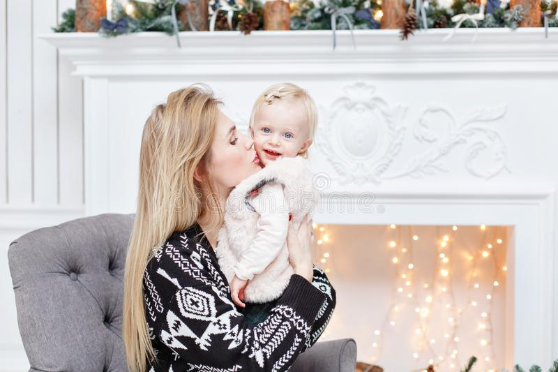 Cheerful mom embraces her cute baby daughter . Parent and little child having fun near Christmas tree indoors. Loving stock photos