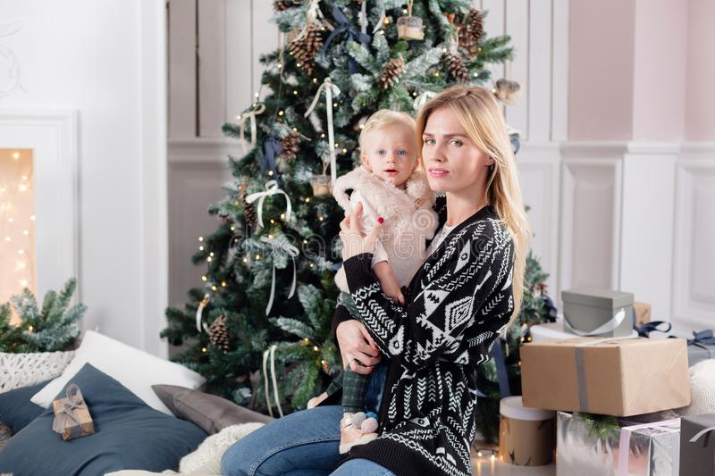 Cheerful mom embraces her cute baby daughter . Parent and little child having fun near Christmas tree indoors. Loving stock photo