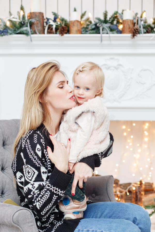 Cheerful mom embraces her cute baby daughter . Parent and little child having fun near Christmas tree indoors. Loving stock images