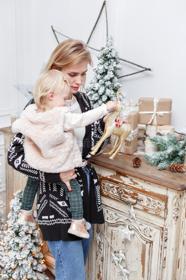 Cheerful mom embraces her cute baby daughter . Parent and little child having fun near Christmas tree indoors. Loving royalty free stock photos