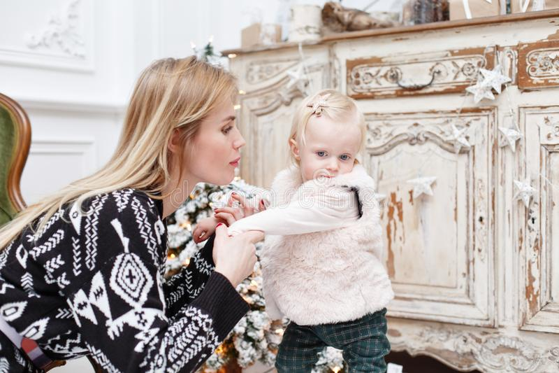 Cheerful mom and her cute daughter. Parent and little child having fun near Christmas tree indoors. Loving family Merry. Cheerful mom and her cute daughter baby royalty free stock photos