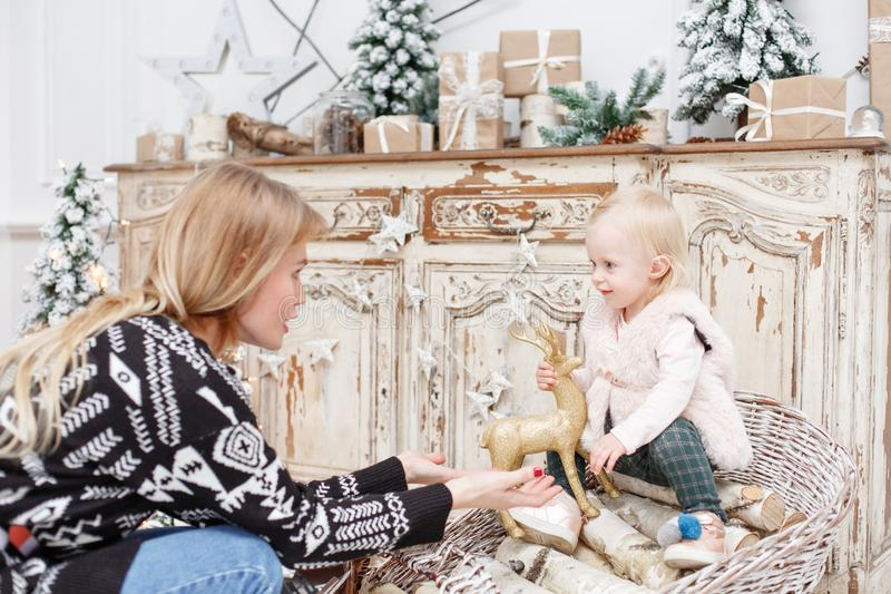 Cheerful mom and her cute daughter. Parent and little child having fun near Christmas tree indoors. Loving family Merry. Cheerful mom and her cute daughter baby royalty free stock photography