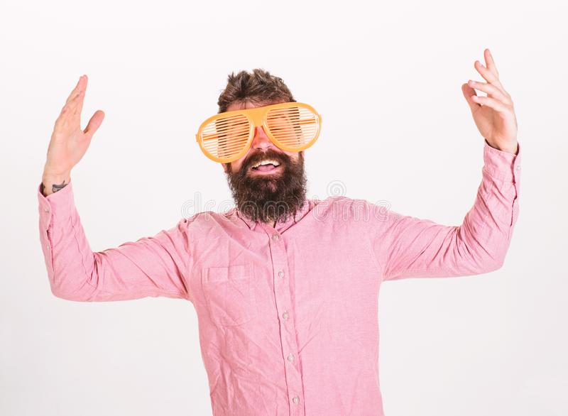 Cheerful mood concept. Hipster looking through of giant striped sunglasses. Guy with beard having fun. Man with beard. And mustache on happy face wears funny royalty free stock photo