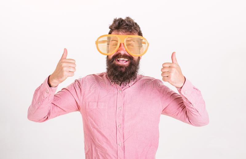 Cheerful mood concept. Hipster looking through of giant striped sunglasses. Guy with beard shows thumbs up. Man with. Beard and mustache on happy face wears stock images