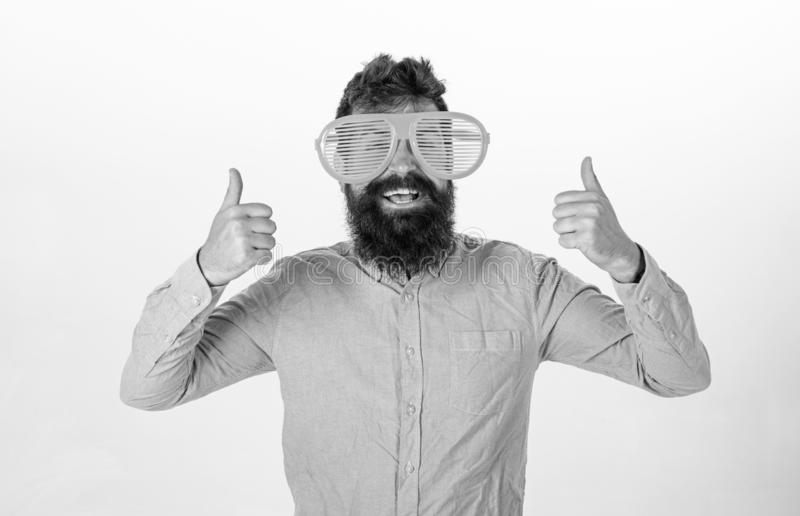Cheerful mood concept. Hipster looking through of giant striped sunglasses. Guy with beard shows thumbs up. Man with. Beard and mustache on happy face wears stock photos