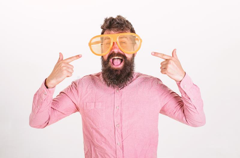 Cheerful mood concept. Hipster looking through of giant striped sunglasses.Man with beard and mustache on happy face. Wears funny big eyeglasses, white royalty free stock photography