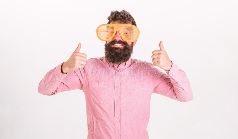 Cheerful mood concept. Hipster looking through of giant striped sunglasses. Man with beard and mustache on happy face. Wears funny big eyeglasses, white royalty free stock images