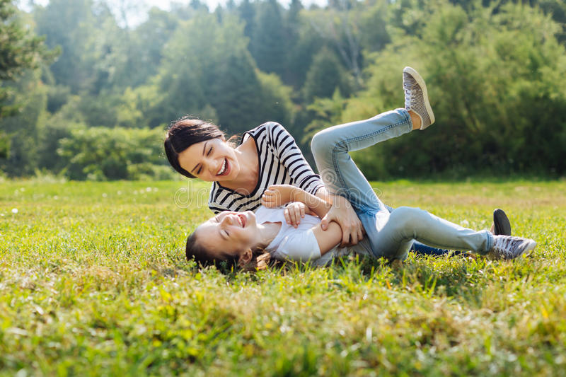 Cheerful mother and daughter goofing around on grass in park stock photos