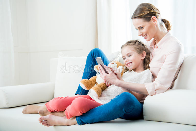 Cheerful mother and daughter using smartphone together royalty free stock photography