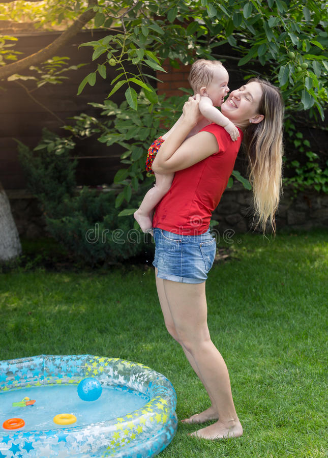 Cheerful mother embracing her baby boy after swimming in pool. Young cheerful mother embracing her baby boy after swimming in pool royalty free stock images
