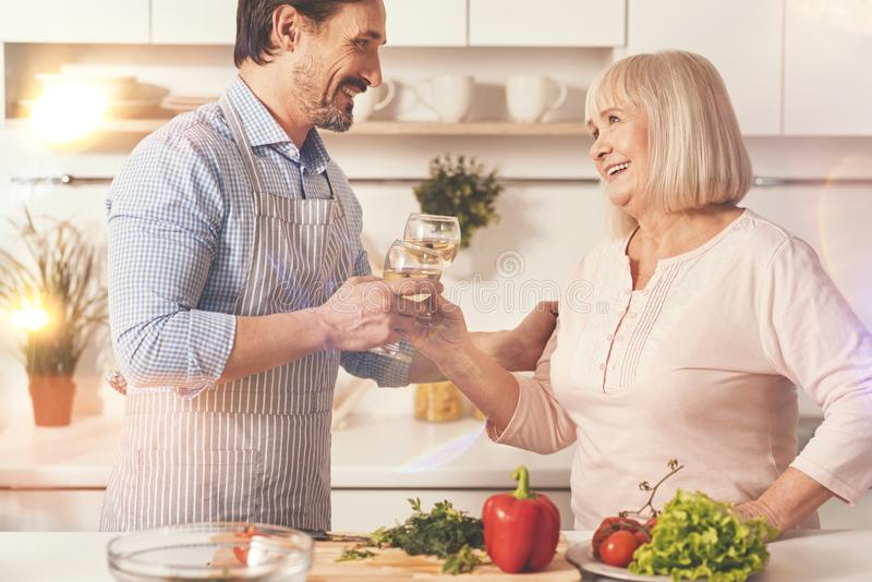 Cheerful mother and her adult son drinking wine royalty free stock photography