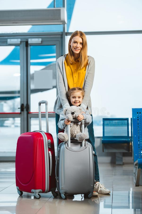 Cheerful mother hugging cute daughter holding teddy bear near baggage stock image