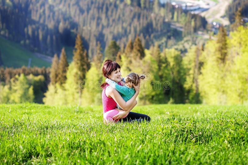 Cheerful mother hugging little girl in nature. The concept of tr royalty free stock images