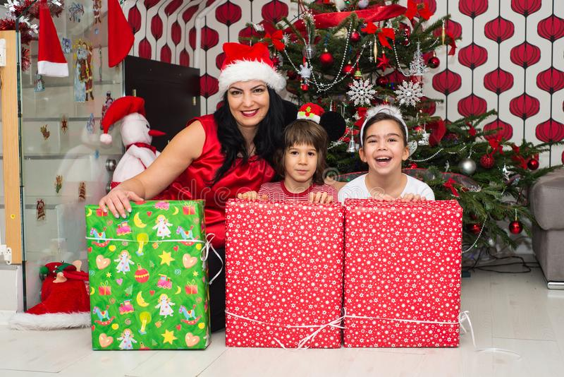 Cheerful mother and kids with presents. Cheerful mother and kids with Christmas presents in front of tree having fun royalty free stock photos