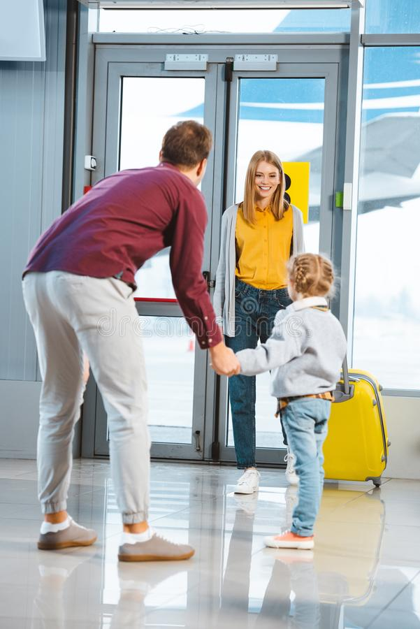 Cheerful mother looking at daughter and husband holding hands stock images