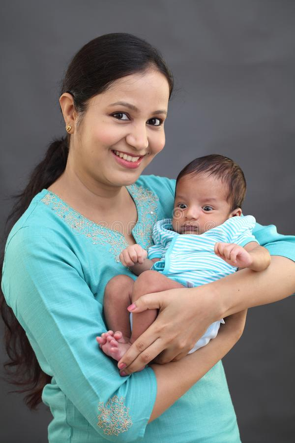 Cheerful mother playing with newborn stock image