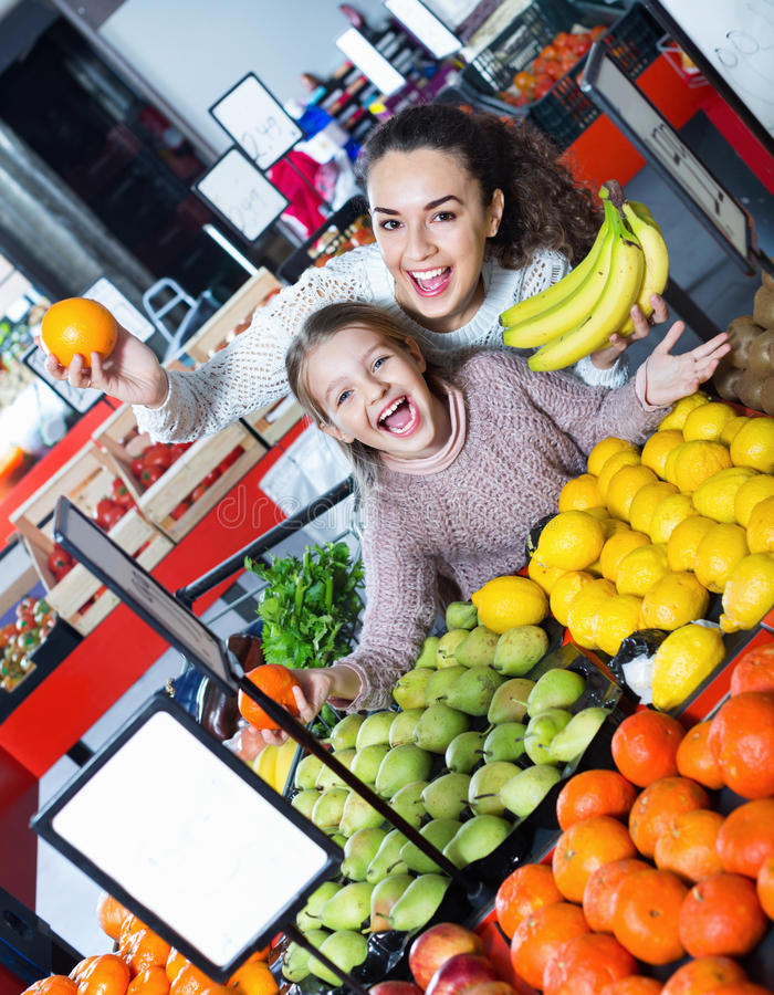 Cheerful mother and smiling little girl choosing fresh fruits. In grocery royalty free stock photo