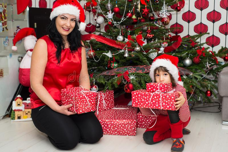 Cheerful mother and son with Christmas gifts. Cheerful mother and son holding Christmas presents and posing in their home stock photography