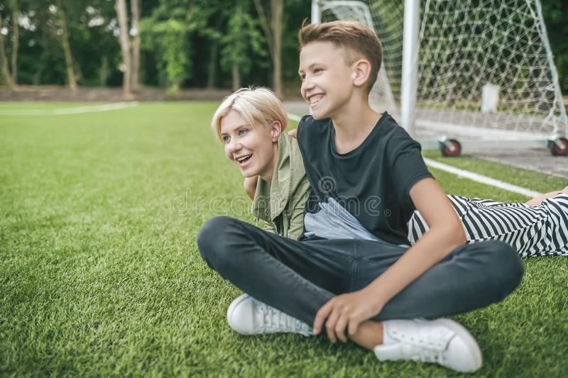 cheerful mother and son laughing and looking away while resting together stock images