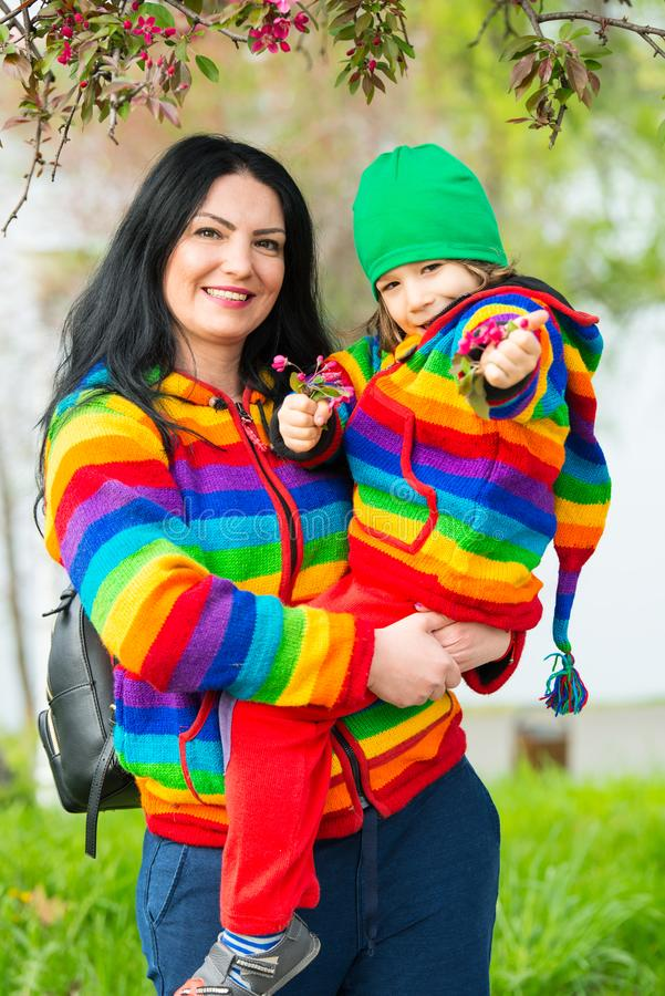 Cheerful mother and son in park. Cheerful mother and son in colorful clothes in park posing together royalty free stock photo