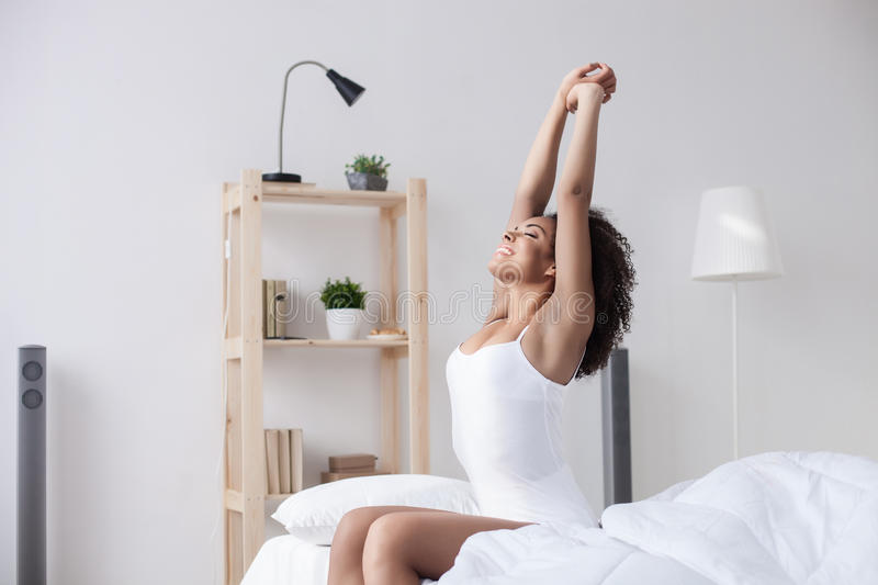 Cheerful mulatto girl is waking up. What a wonderful morning. Attractive young african woman is stretching arms after sleeping. She is sitting on bed and smiling stock image