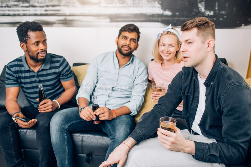Cheerful multi-ethnic friends sitting on sofa stock photography
